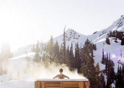woman in hot tub with mountain backdrop and snow covered mountain